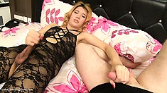 The horny shemale in a sexy black bodysuit puts into action her handjob skills
