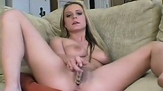 Hot blonde with big tits Chelsea lies on the couch and bangs her twat with a glass dildo