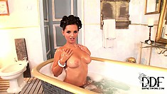 Busty brunette takes a bubble bath and shows off and fingers her cunt
