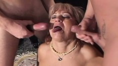 Horny granny getting pounded by two young studs in the living room