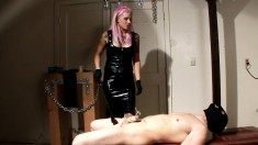 Mistress Nightshadow wears black leather to punish a male slave in bondage