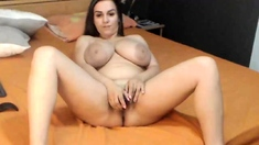 Busty brunette with a big booty toys herself on cam